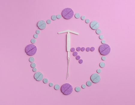 The concept time of replacement of the contraceptive intrauterine device, IUD. Glamorous birth control pills on a pink background, paper art