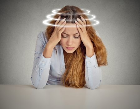Woman with vertigo. Young female patient suffering from dizziness.