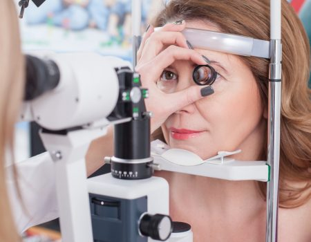 Skillful oculist is examining female eye with the help of a slit lamp. She is holding lens near the human eye. The woman is sitting and gently smiling
